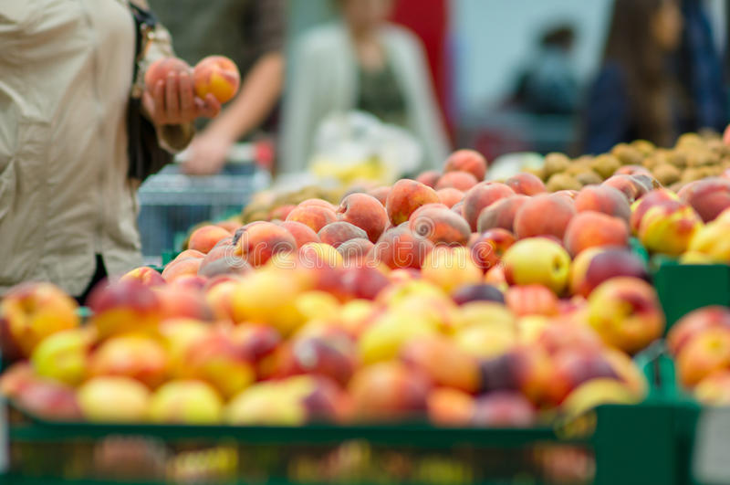 Customers selecting peaches in supermarket stock images