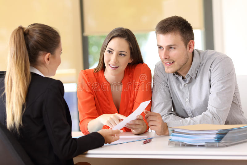 Customers solving doubts about contract at office. Two happy customers solving doubts about a contract with the saleswoman at office royalty free stock image