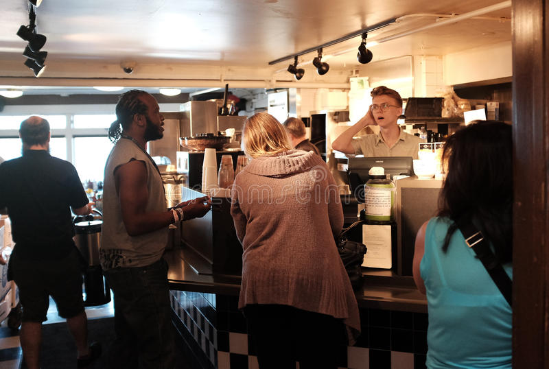 Customers talk with barista at coffee bar in Pike Place Market, Seattle stock photography