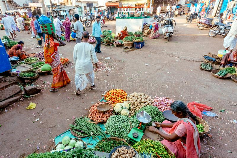 Customers in traditional dresses buying fresh green peas, potatoes, carrots at market of indian street royalty free stock images