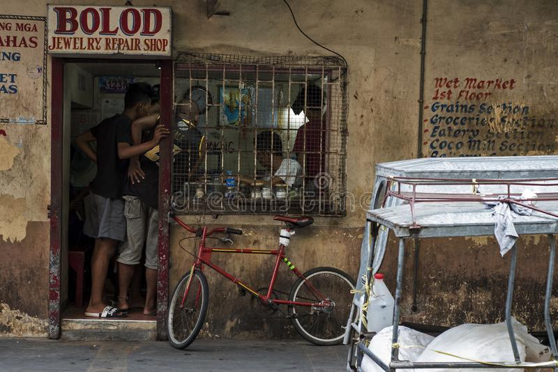 Customers wait at an old jewelry repair shop, with a tuk-tuk in front of the shop in Tabaco, the Philippines royalty free stock photography