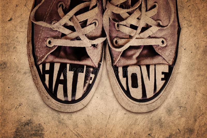 Customized used sneakers with words hate and love on grunge texture background royalty free stock image