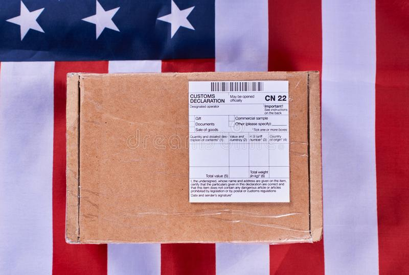 Customs declaration concept. Parcel with Customs declaration form CN22 on American flag background. Gneral view royalty free stock photos
