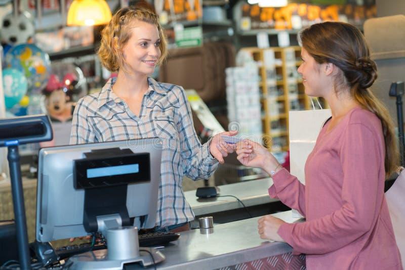 Custormer femenino usando el terminal de la tarjeta de crédito en el pago y envío fotos de archivo