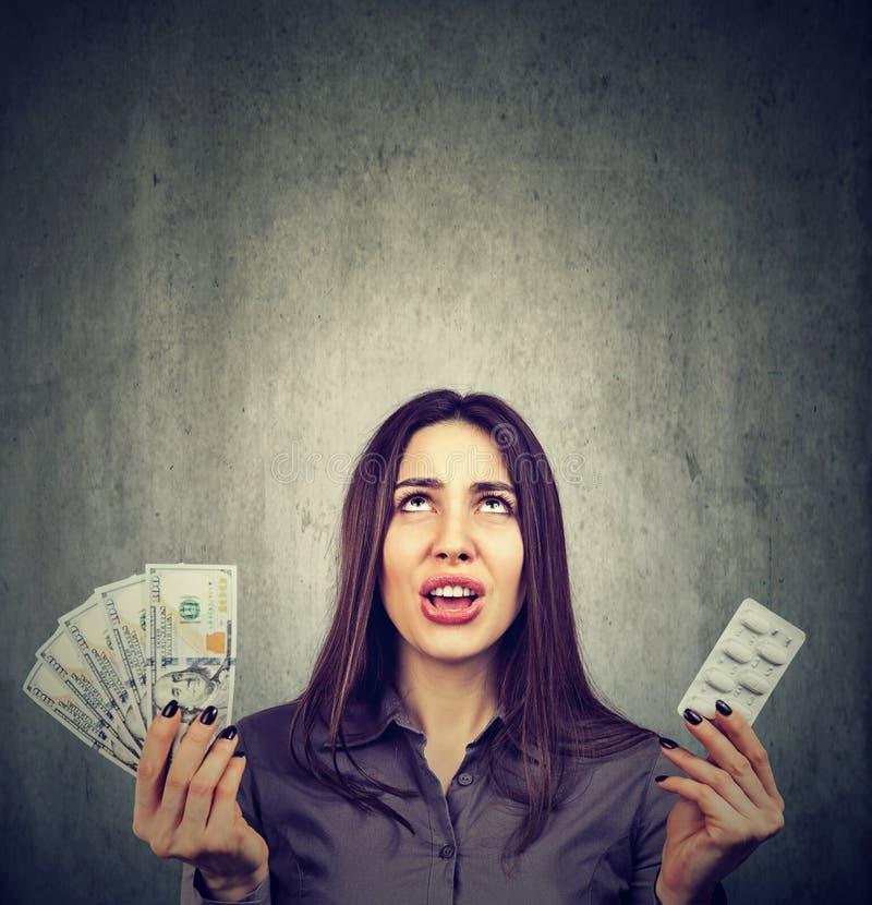 Custos dos cuidados médicos Mulher frustrante com comprimidos e cédulas do dólar imagens de stock royalty free
