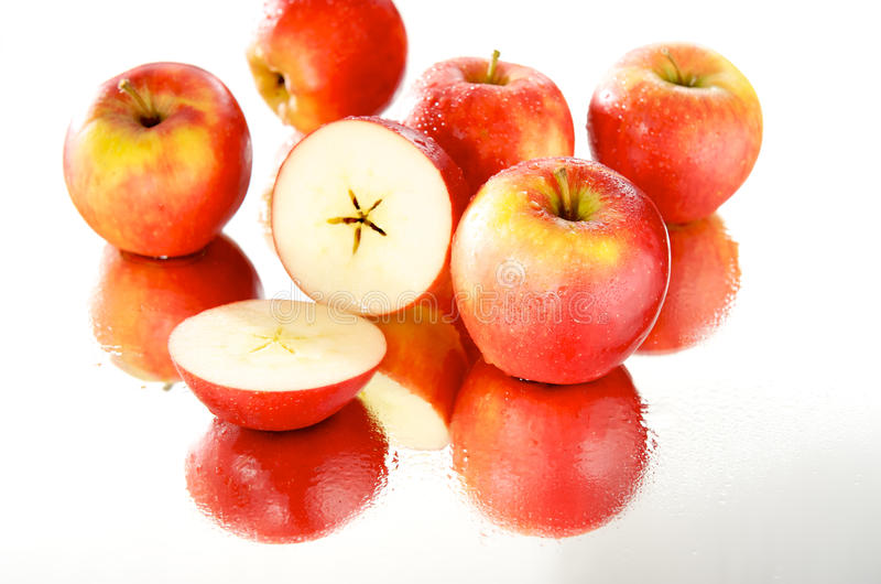 Cut apple in wet group, mirror royalty free stock images