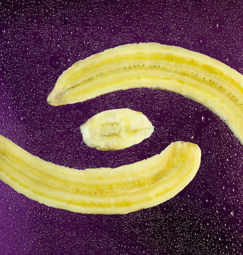 Cut banana purple color. Abstract image of the cosmos in the form of a longitudinal piece of a banana horizontally on a purple background with bubbles royalty free stock photography