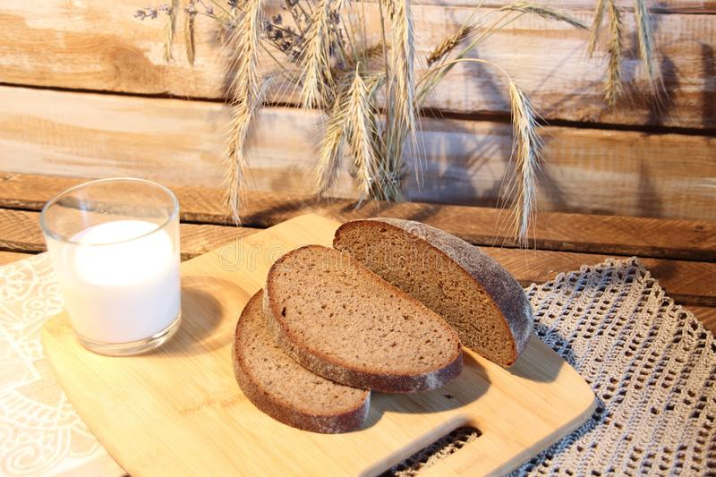 Cut brown bread on wooden board, glass of milk and spicas in rustic style royalty free stock photos