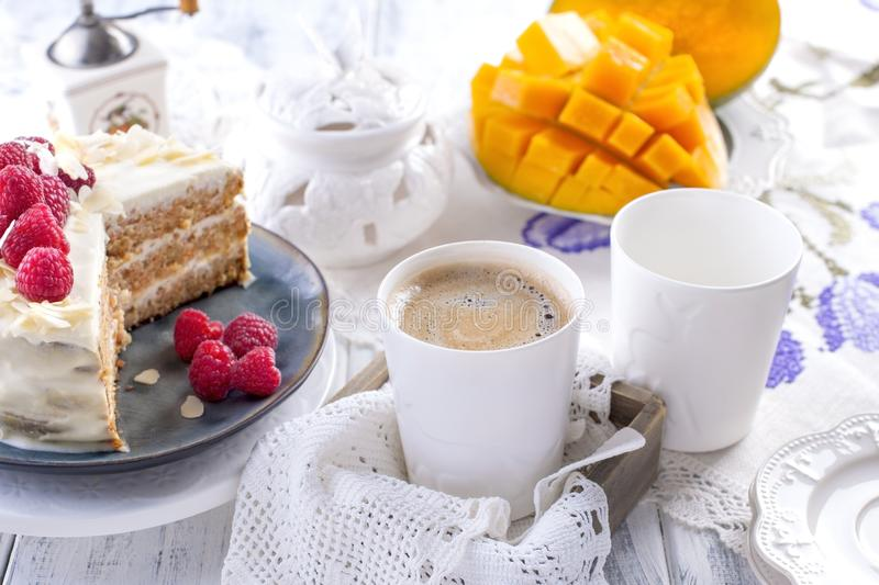 Cut the cake with white cream, for breakfast. A mango fruit. White background, tablecloth with lace, a cup of fragrant black royalty free stock photography