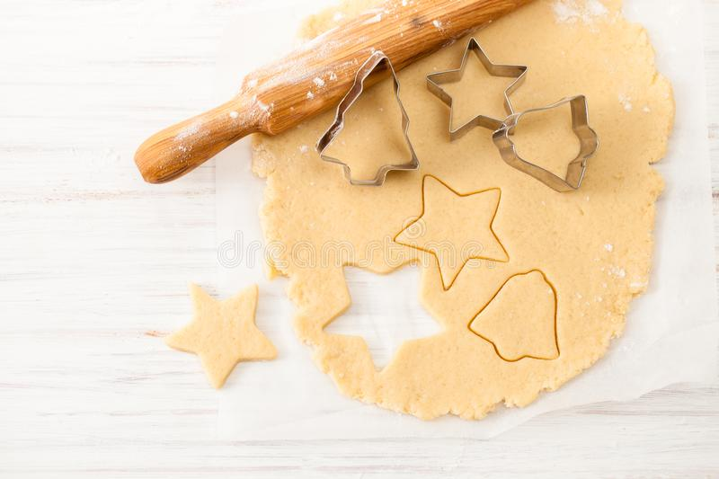 Cut the cookie shape from the dough at the white table. View with copy space royalty free stock photos