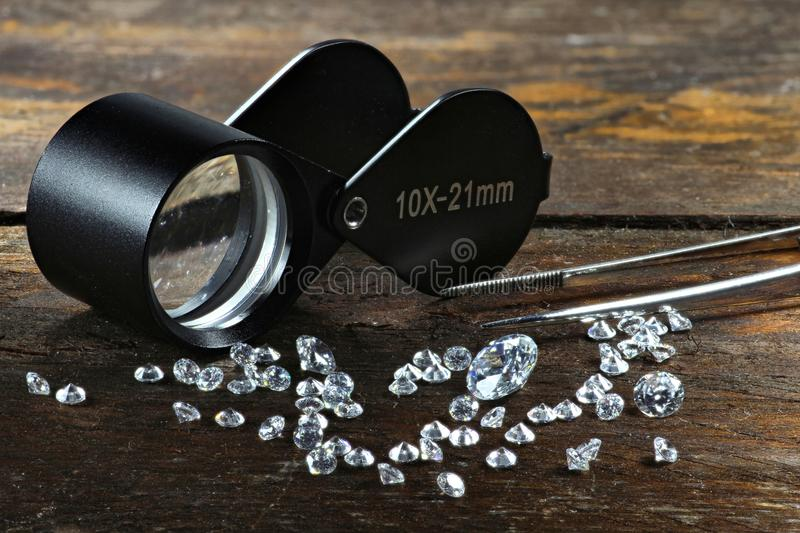 Cut diamonds. With folding magnifier and tweezers on wooden background stock photos