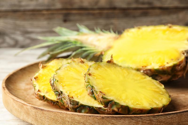 Cut fresh juicy pineapple on wooden tray. Closeup royalty free stock image