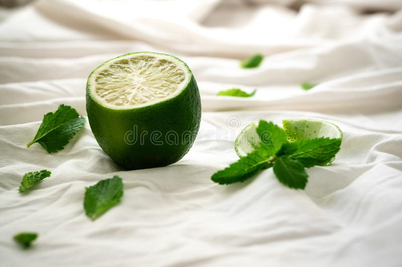Cut green fruit for making smoothies, teas and beverages for healthy eating. Still life with lime and mint on a white tablecloth. Cut green fruit for making stock photography