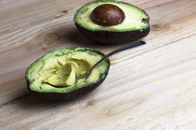Cut in half avocado with a spoon. On wooden background royalty free stock photos