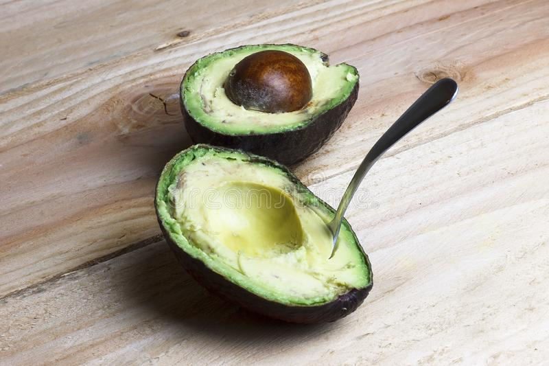 Cut in half avocado with a spoon. On wooden background stock photo