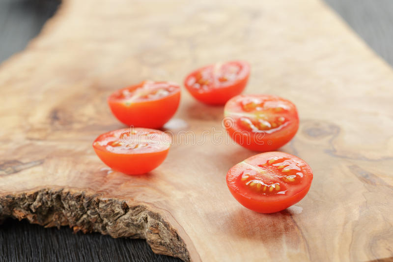 Cut in half cherry tomatoes on wood table royalty free stock images