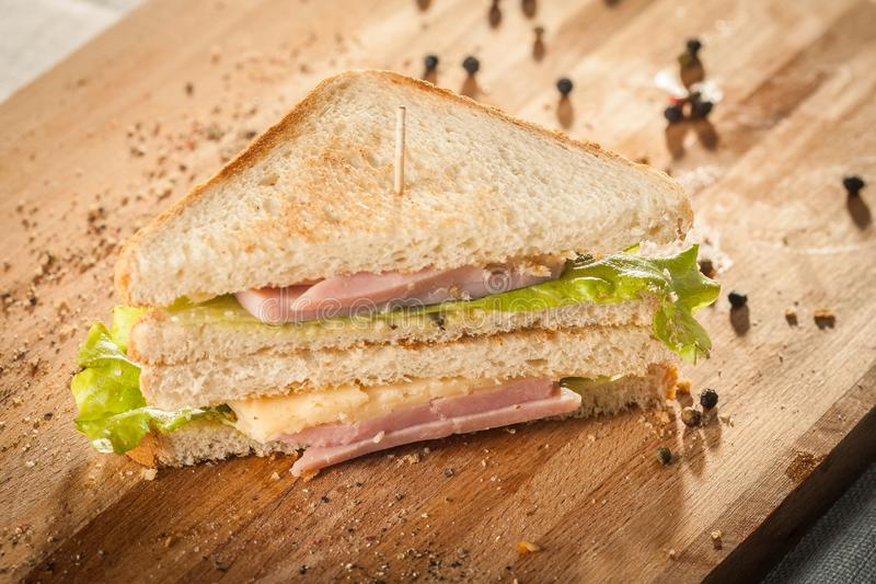 Cut by half sandwich with cheese, salad and ham royalty free stock photography