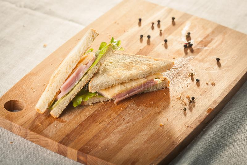 Cut by half sandwich with cheese, salad and ham stock images