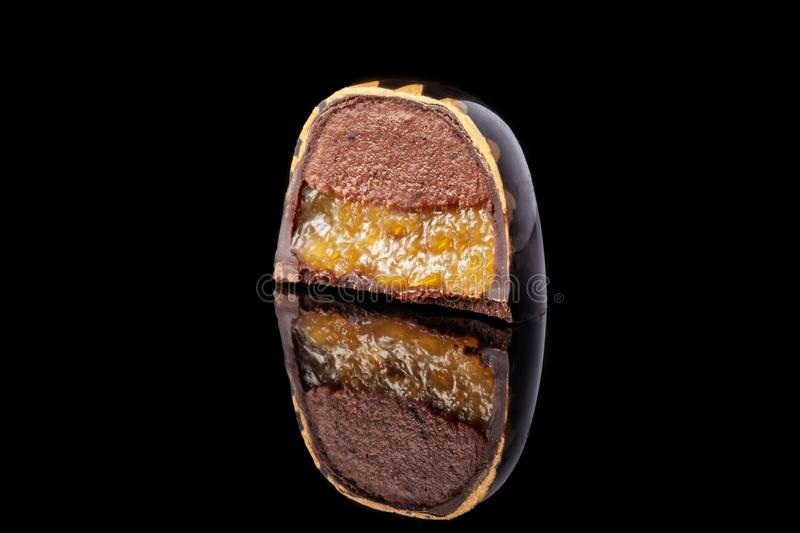 Cut luxury handmade candy with chocolate and yellow confiture filling on black background. stock image