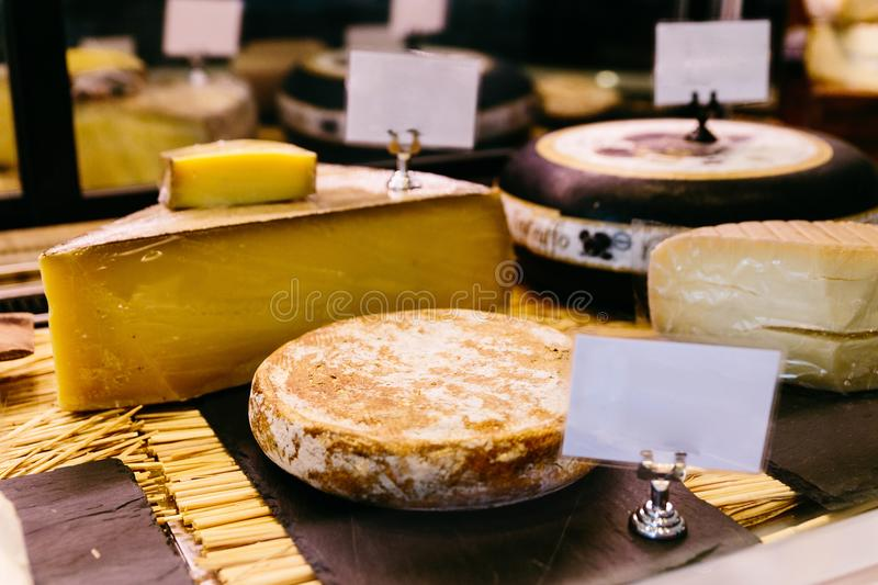 Cut many kind of cheese wheels for sell stock images