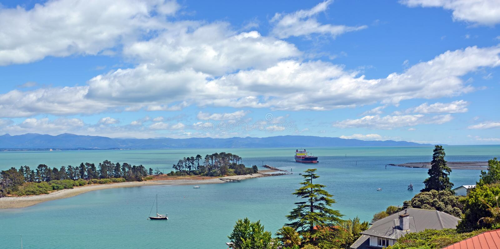 The Cut - Nelson, New Zealand. A container ship sails through the famous Cut - between Haulashore Island and The Boulder Bank in Nelson, New Zealand stock images