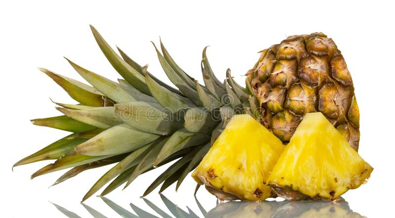 Cut off top of pineapple with leaves, next to slices isolated on white royalty free stock images