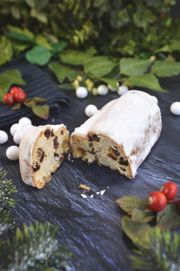 Cut open traditional German christmas season sweet food called `Stollen` or `Christstollen`. A fruit bread of nuts, spices, and dried or candied fruit, coated stock photo