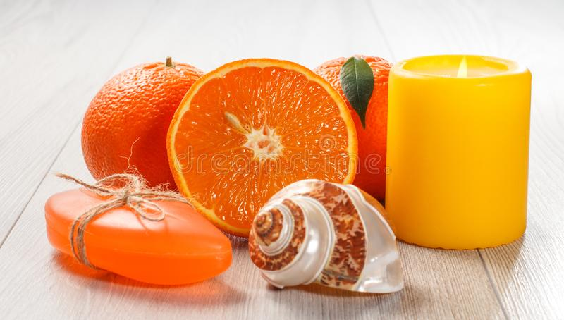 Cut orange with two whole oranges, soap, sea shell and burning candle. On wooden desk. Spa products and accessories stock photography