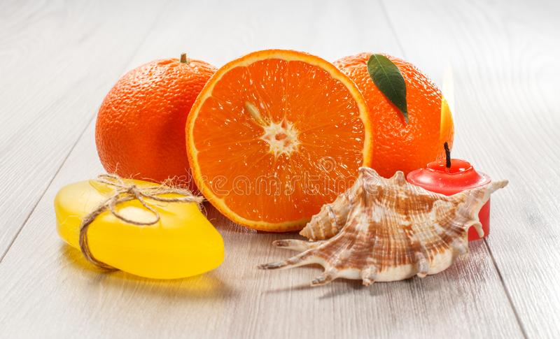 Cut orange with two whole oranges, soap, sea shell and burning candle. Cut orange with two whole oranges, soap, sea shell and burning red candle on wooden desk royalty free stock photography