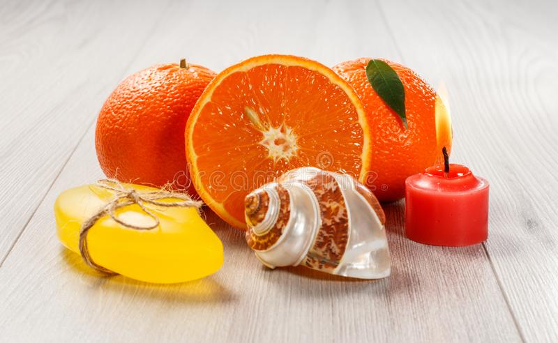 Cut orange with two whole oranges, soap, sea shell and burning candle. Cut orange with two whole oranges, soap, sea shell and burning red candle on wooden desk stock photos