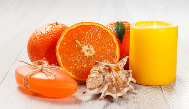 Cut orange with two whole oranges, soap, sea shell and burning candle. On wooden desk. Spa products and accessories stock image