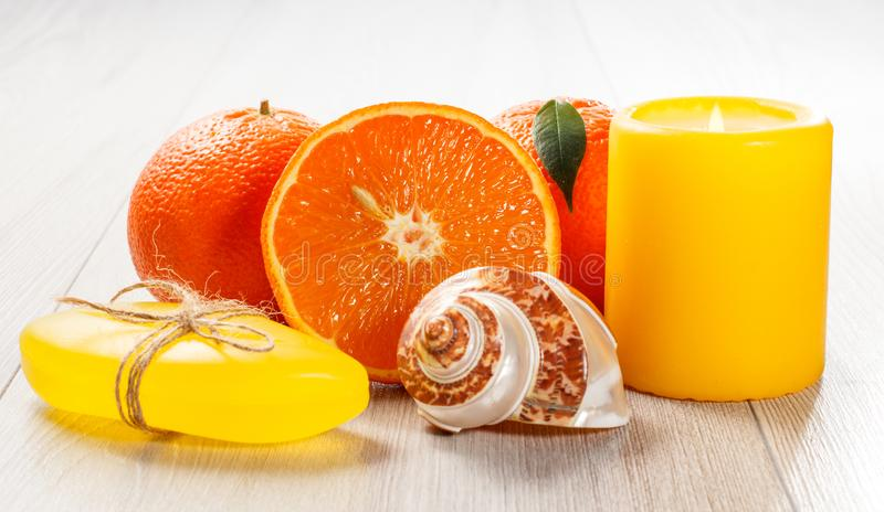 Cut orange with two whole oranges, soap, sea shell and burning candle. On wooden desk. Spa products and accessories royalty free stock image