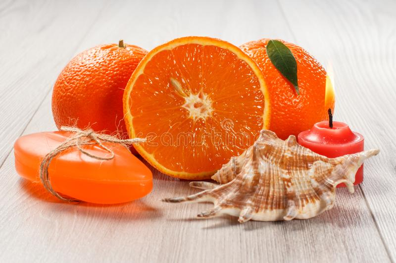 Cut orange with two whole oranges, soap, sea shell and burning c. Cut orange with two whole oranges, soap, sea shell and burning red candle on wooden desk. Spa royalty free stock photography
