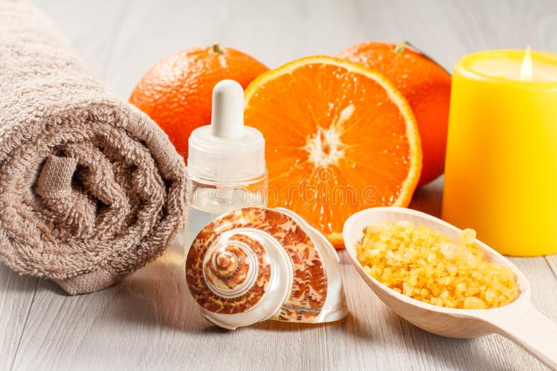 Cut orange with two whole oranges, towel, sea shell, bottle with aromatherapy oil, wooden spoon with yellow sea salt and burning. Candle on wooden desk. Spa royalty free stock photos