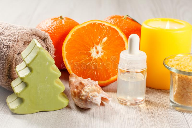 Cut orange with two whole oranges, towel, soap, sea shell, bottle with aromatherapy oil, glass bowl with yellow sea salt and. Burning candle on wooden desk. Spa stock photo