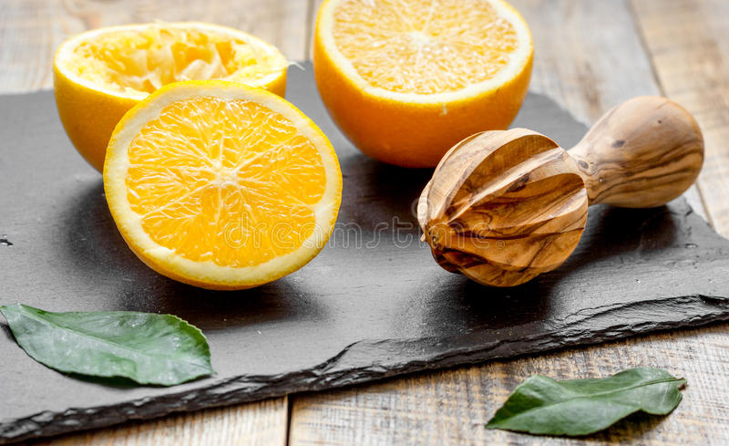 Cut oranges in half and juicer on wooden background. Wooden background close up stock photography