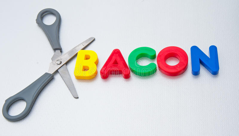 Cut out bacon. Scissors alongside text 'bacon' in colorful uppercase letters, white background. Concept of medical advice on perils of eating bacon stock images