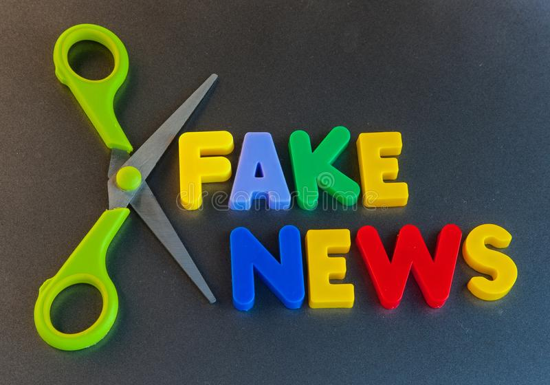 Cut out fake news. Text `cut out fake news` in colorful uppercase letters surrounded by the blades of a pair of scissors. Concept of upsetting the democratic stock images