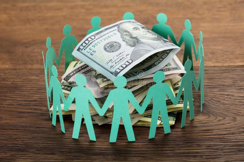Cut-out Figures Around The Hundred Dollar Bill stock photography