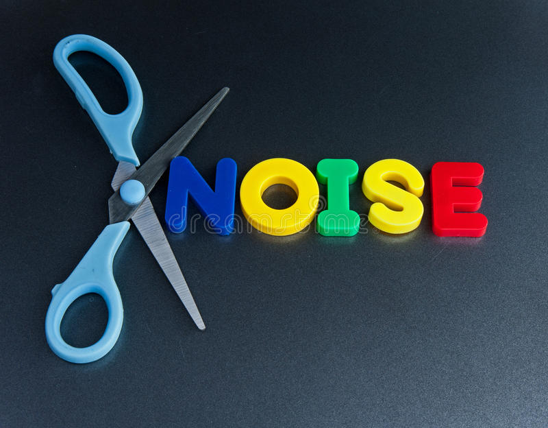 Cut out noise. Text Cut out noise in colorful uppercase letters with scissors alongside indicating cut or reduction, dark background royalty free stock image