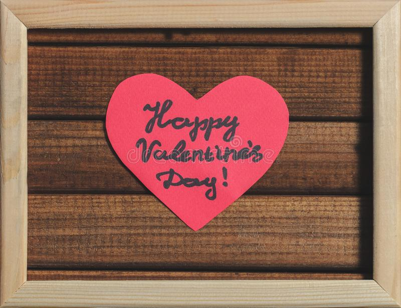 Cut out of red paper hearts on wooden background in wooden frame, greetings happy Valentine`s day stock image