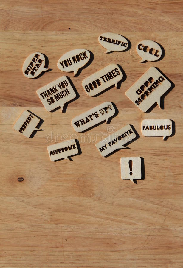 Cut out words on wood background. Several words and phrases cut from thin wood on warm toned background stock photo