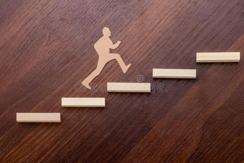 Cut outs of paper man climbing the steps to success in a concept. Ual image over wooden background royalty free stock image