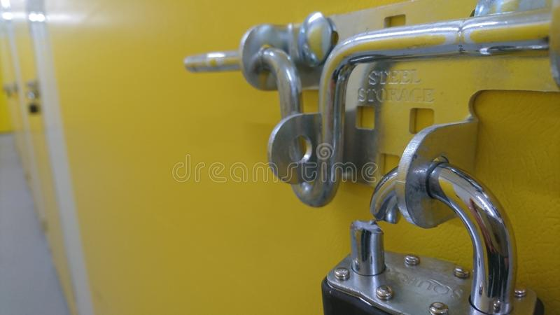 A cut padlock on an unpaid storage unit door. Tin pathway doorway padlock silver shiny locked closed hunters trolley corridor protection end of the corridor bolt royalty free stock photography