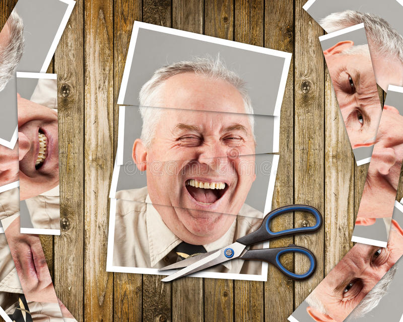 Cut photos. Laughing face put together from cut pictures, on wooden background royalty free stock images