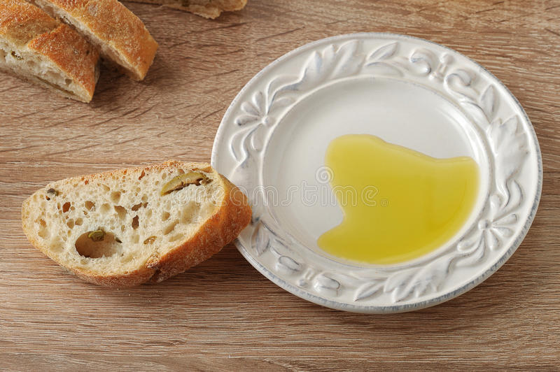 Cut into pieces ciabatta with olives and olive oil in a saucer royalty free stock images