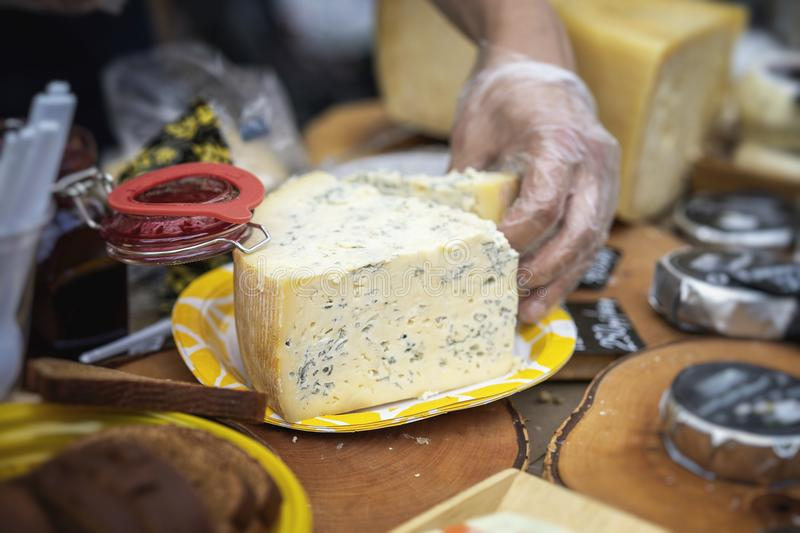 Cut pieces genuine cheese, farmer market. Piece of cheese with blue mold and hand of seller, market counter, real scene. Cut pieces genuine cheese, assortment at stock photography