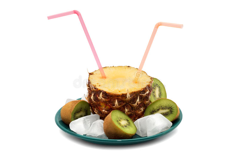 Cut pineapple with two pink tubes on a green plate, surrounded by a kiwi cut in half and ice cubes stock image
