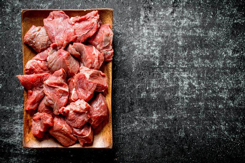 Cut raw beef in a wooden plate. On black rustic background stock image