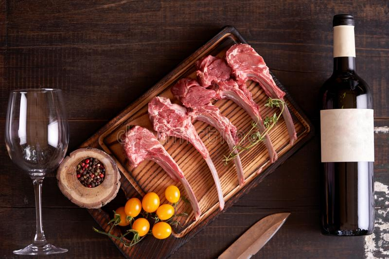 Cut raw rack of lamb on a cutting wooden board with yellow tomatoes, colorful peas, a bottle of red wine and a wine glass. Lying next to it royalty free stock photography